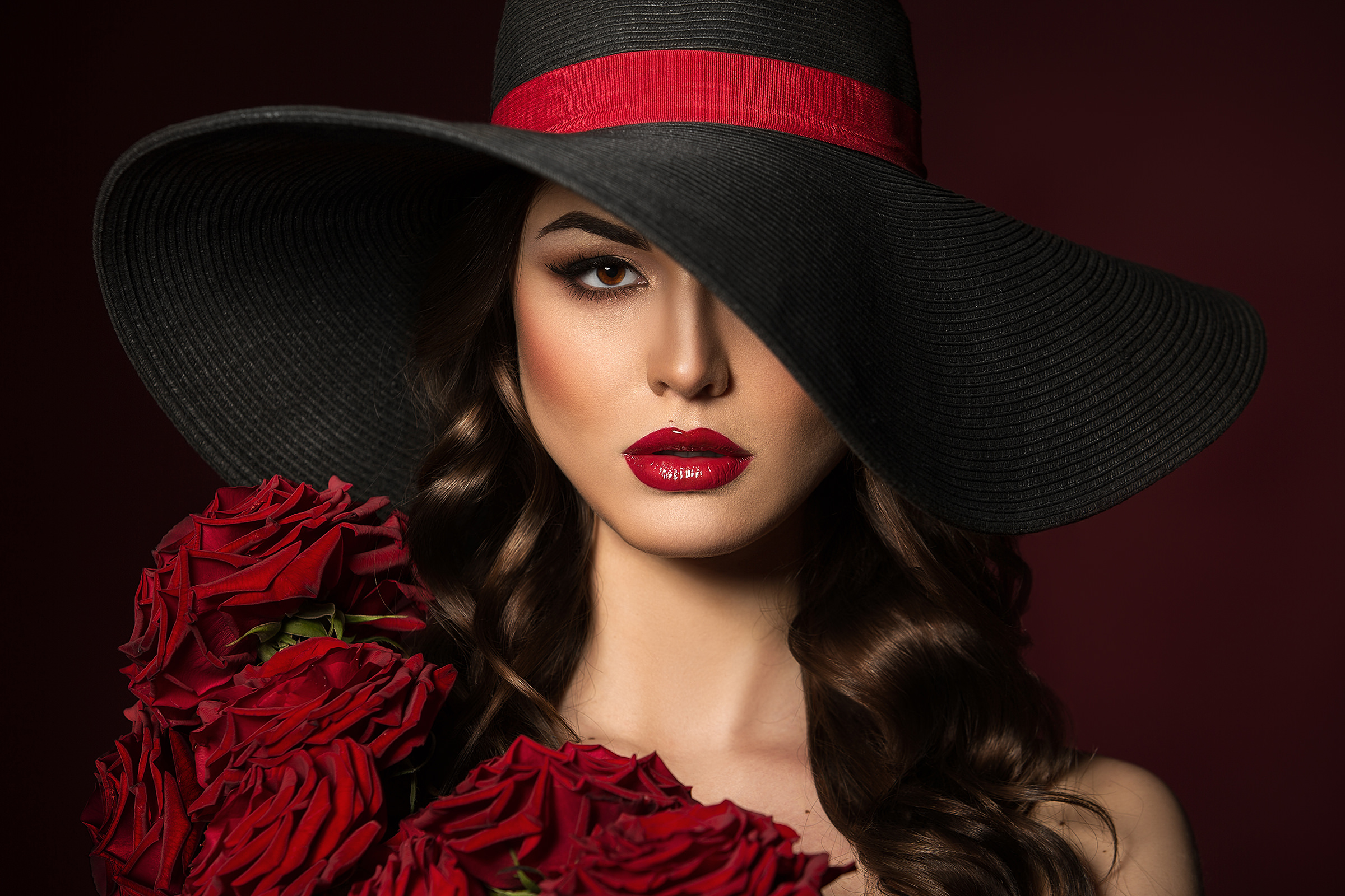 Portrait of a beautiful woman in a black hat with red roses on the shoulders. Red Lips. Beautiful Hair.